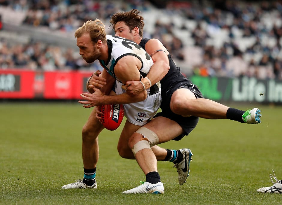MELBOURNE, AUSTRALIA - JUNE 30: Jack Hombsch of the Power is tackled by Levi Casboult of the Blues during the 2018 AFL round15 match between the Carlton Blues and the Port Adelaide Power at the Melbourne Cricket Ground on June 30, 2018 in Melbourne, Australia. (Photo by Michael Willson/AFL Media)
