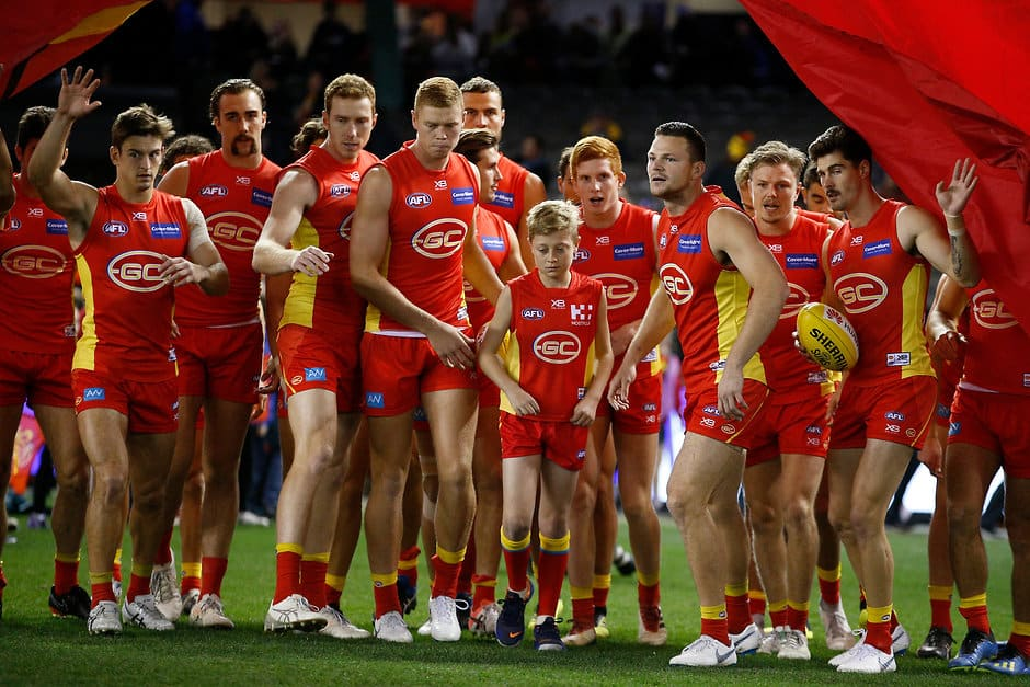 MELBOURNE, AUSTRALIA - JULY 08: Suns players run through the banner during the 2018 AFL round 16 match between the North Melbourne Kangaroos and the Gold Coast Suns at Etihad Stadium on July 08, 2018 in Melbourne, Australia. (Photo by Daniel Pockett/AFL Media)