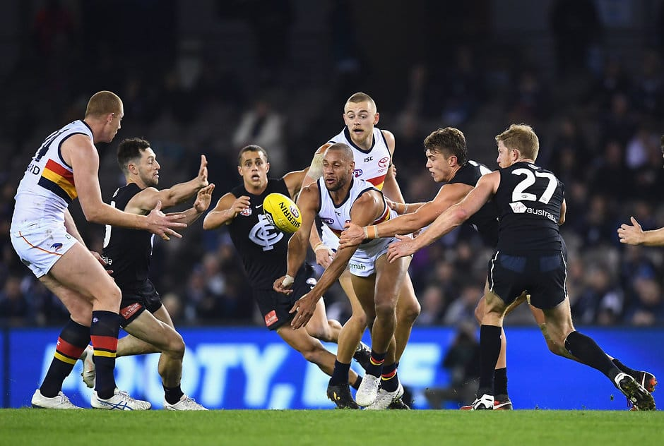 MELBOURNE, AUSTRALIA - AUGUST 25:  Cam Ellis-Yolmen of the Crows handballs whilst being tackled during the round 23 AFL match between the Carlton Blues and the Adelaide Crows at Etihad Stadium on August 25, 2018 in Melbourne, Australia.  (Photo by Quinn Rooney/Getty Images/AFL Media)