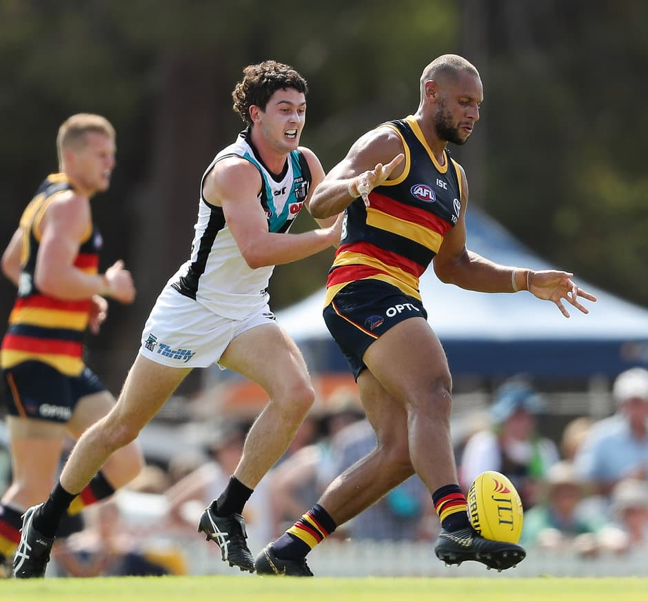 ADELAIDE, AUSTRALIA - MARCH 02 : Cameron Ellis-Yolmen of the Crows kicks the ball in front of Darcy Byrne-Jones of the Power during the 2019 JLT Community Series match between the Adelaide Crows and the Port Adelaide Power at Memorial Oval on March 02, 2019 in Adelaide, Australia. (Photo by AFL Media)