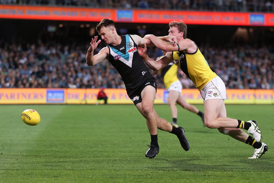 ADELAIDE, AUSTRALIA - APRIL 13: Robbie Gray of the Power is held by Dylan Grimes of the Tigers during the 2019 AFL round 04 match between the Port Adelaide Power and the Richmond Tigers at Adelaide Oval on April 13, 2019 in Adelaide, Australia. (Photo by AFL Photos)