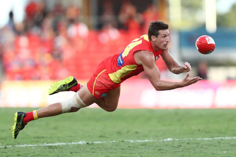 GOLD COAST, AUSTRALIA - APRIL 27: David Swallow of the Suns handballs during the round 6 AFL match between Gold Coast and Brisbane at Metricon Stadium on April 27, 2019 in Gold Coast, Australia. (Photo by Chris Hyde/Getty Images)