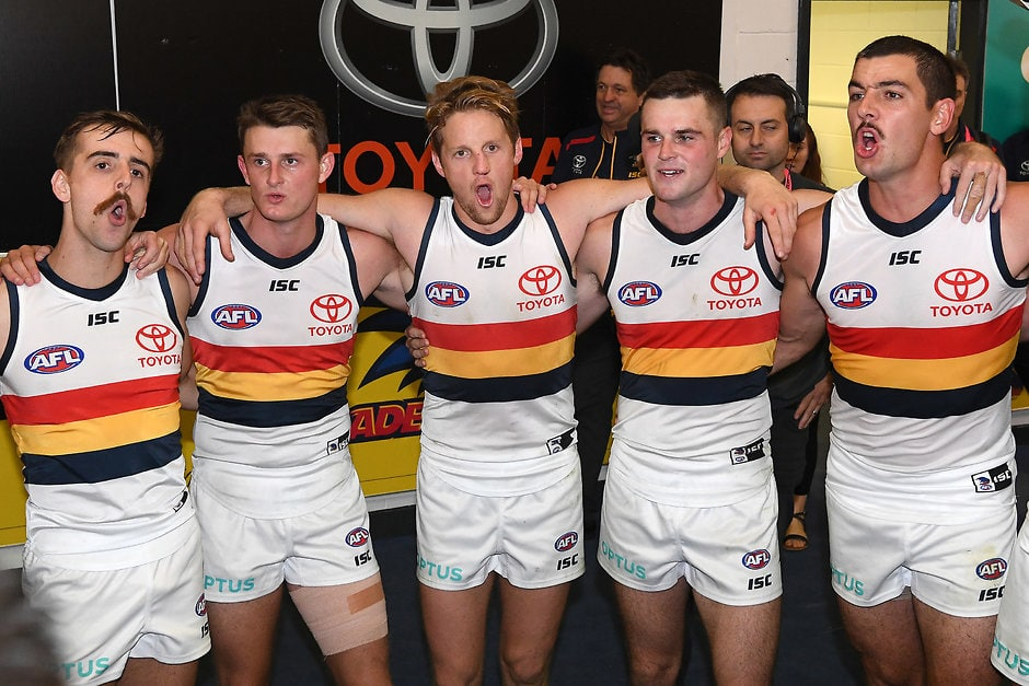 MELBOURNE, AUSTRALIA - APRIL 27: Jordan Gallucci, Matt Crouch, Rory Sloane, Brad Crouch and Taylor Walker of the Crows sing the song in the rooms after winning the round 6 AFL match between St Kilda and Adelaide at Marvel Stadium on April 27, 2019 in Melbourne, Australia. (Photo by Quinn Rooney/Getty Images)