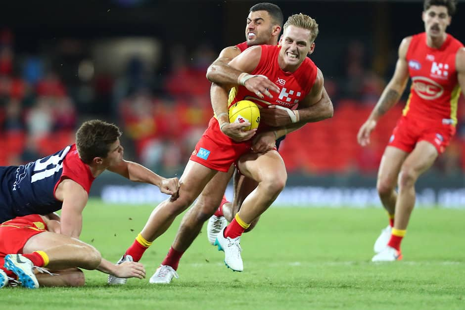 GOLD COAST, AUSTRALIA - MAY 11: Darcy Macpherson of the Suns is tackled during the round eight AFL match between the Gold Coast Suns and the Melbourne Demons at Metricon Stadium on May 11, 2019 in Gold Coast, Australia. (Photo by Chris Hyde/Getty Images)