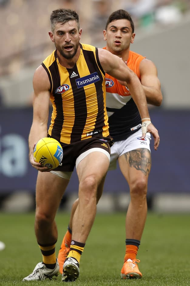 MELBOURNE, AUSTRALIA - MAY 12: Ricky Henderson of the Hawks handpasses the ball ahead of Tim Taranto of the Giants during the 2019 AFL round 08 match between the Hawthorn Hawks and the GWS Giants at the Melbourne Cricket Ground on May 12, 2019 in Melbourne, Australia. (Photo by Dylan Burns/AFL Photos)