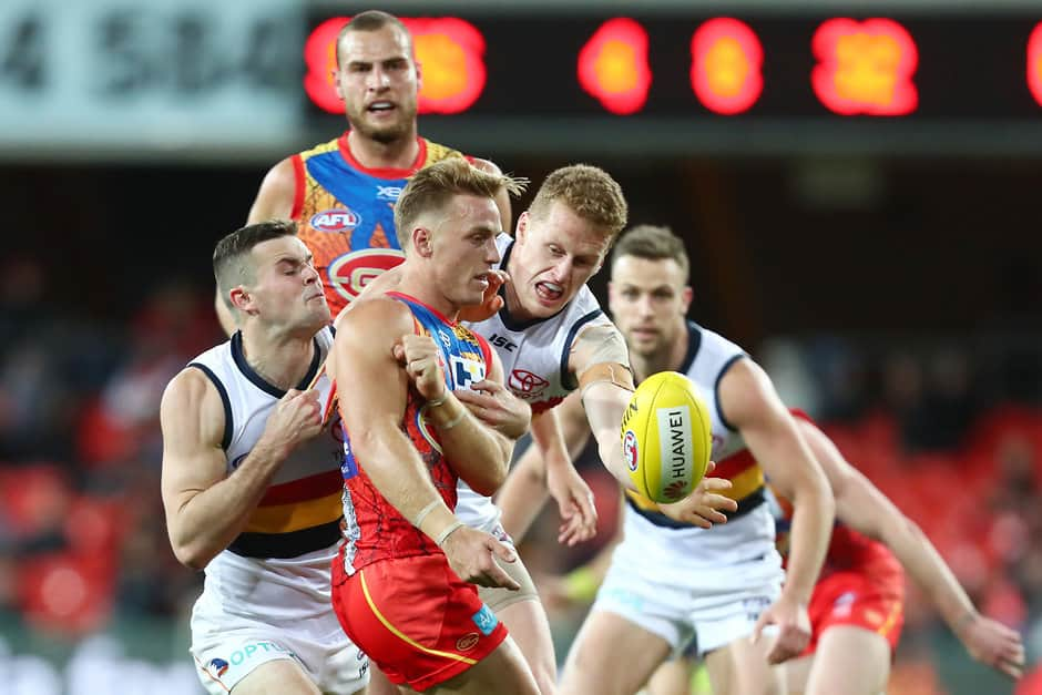 GOLD COAST, AUSTRALIA - JULY 13: Darcy Macpherson of the Suns is tackled during the round 17 AFL match between the Gold Coast Suns and the Adelaide Crows at Metricon Stadium on July 13, 2019 in Gold Coast, Australia. (Photo by Chris Hyde/Getty Images via AFL Photos)